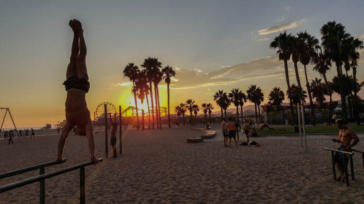 Handstand auf den P-Bars während dem Sonnenuntergang in Santa Monica